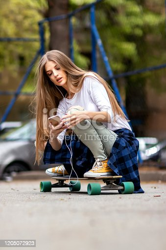 625928750 istock photo Having fun . Female Skateboarder is Using a Mobile Phone in the Street 1205072923