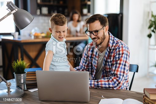 Smiling father and son using laptop at home