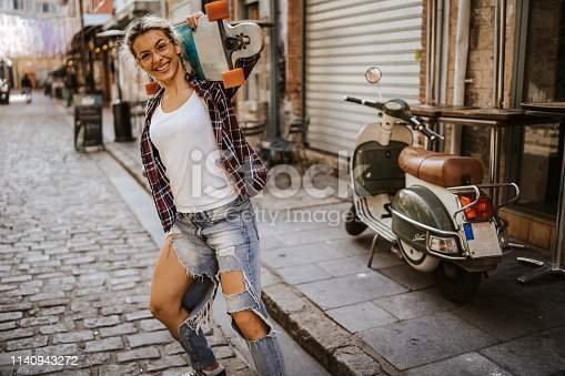 Beautiful young blond woman leaning on her scooter