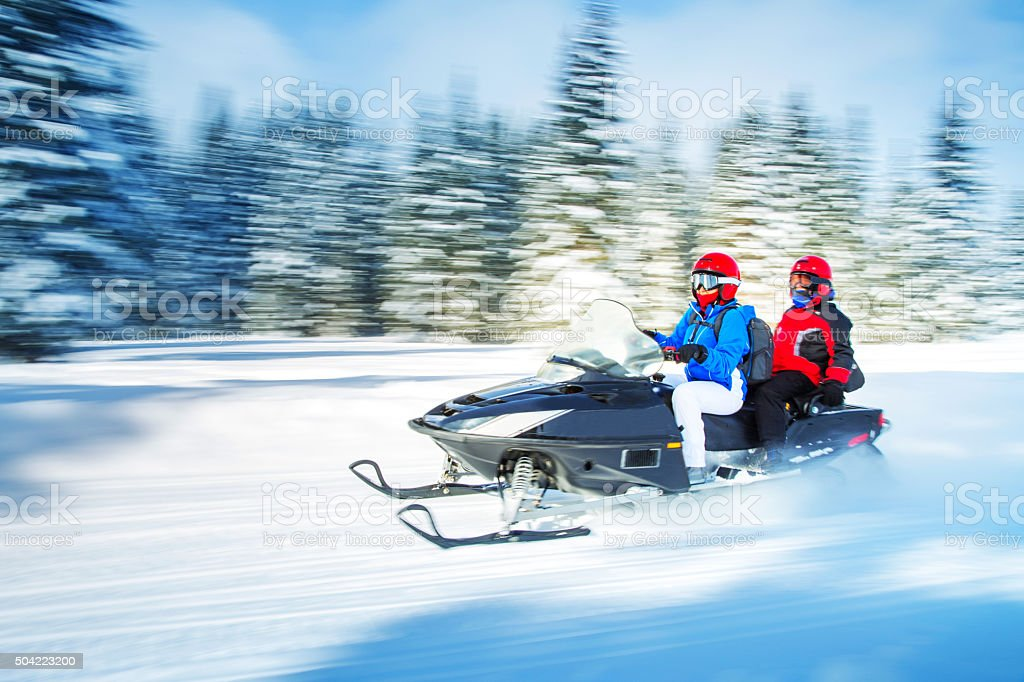Woman and kid driving a snowmobile in Colorado, USA - panning motion...