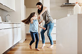Shot of an adorable little girl dancing with her mother at home