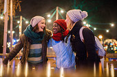 Photo of a cheerful friends spending time on Christmas market during holidays
