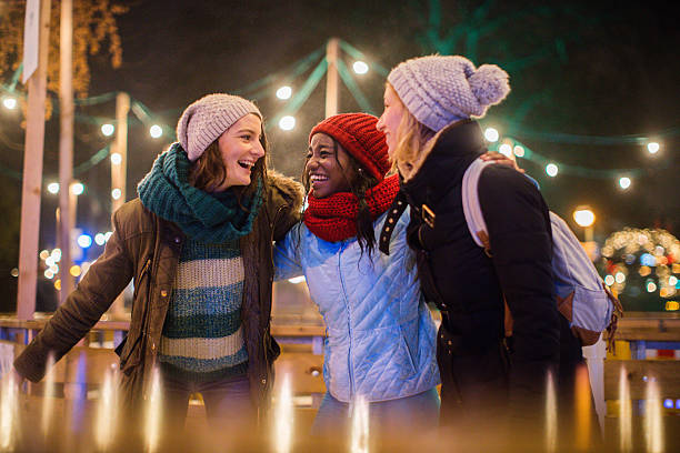 Having fun on Christmas market Photo of a cheerful friends spending time on Christmas market during holidays  ice skating stock pictures, royalty-free photos & images