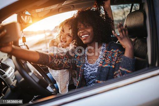 Traveler friends taking selfie in car