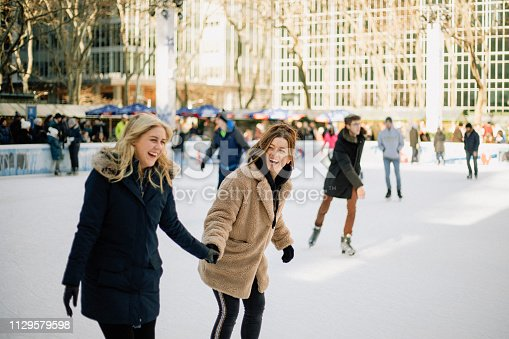 A front-view shot of two mid-adult women ice skating together in an ice rink in New York City, they are wearing warm clothing, holding hands and laughing together.