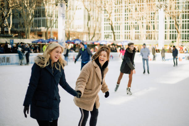 Having Fun on the Ice Rink A front-view shot of two mid-adult women ice skating together in an ice rink in New York City, they are wearing warm clothing, holding hands and laughing together. ice rink stock pictures, royalty-free photos & images