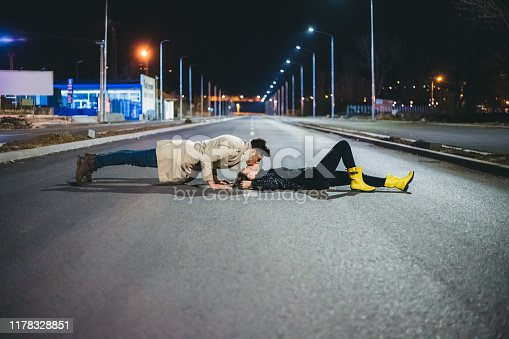 Young Caucasian heterosexual couple is having fun on an empty street at night.