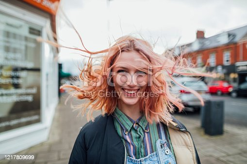 Woman standing outdoors looking away from the camera while her hair blows in the wind.