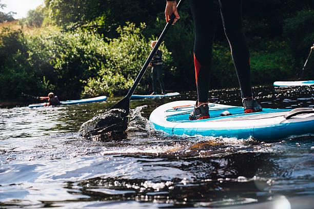 having fun paddleboarding - stehpaddeln stock-fotos und bilder