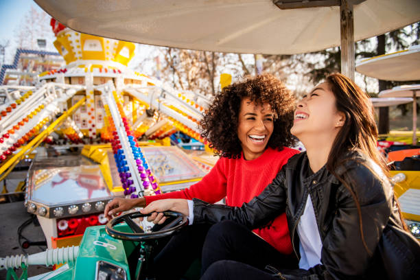 Having fun. Two friends riding amusement park ride traveling carnival stock pictures, royalty-free photos & images