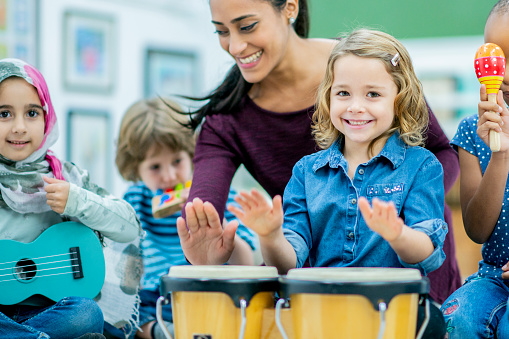 A diverse group of students plays musical instruments in preschool class with their teacher, who is smiling.