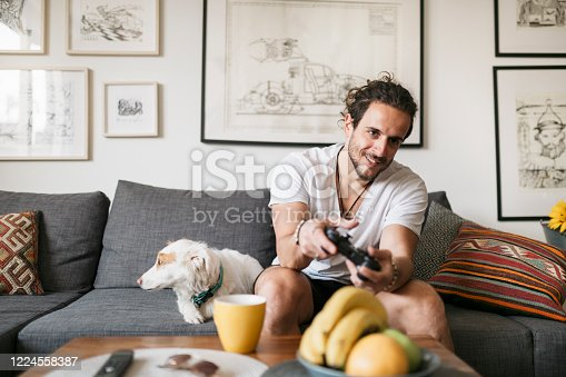 Young man, a gamer sitting in his living room with his dog, holding a controller, playing video games and smiling.