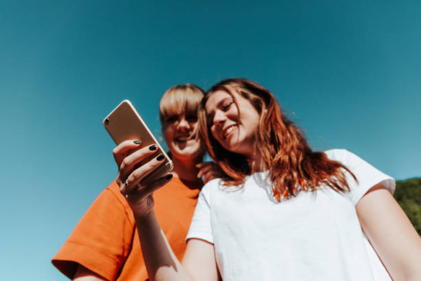 Having Fun Student Girls Reading Messages On Mobile Phone stock photo