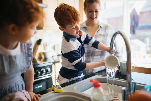 Having Fun Washing the Dishes Two children and their Mother washing the dishes in the kitchen sink. chores stock pictures, royalty-free photos & images