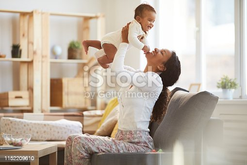 Jolly excited young African woman with pony tail enjoying maternity and having fun with baby son at home