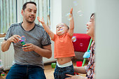 An adorable mixed-race boy is playing with his father and mother as they blow bubbles through a bubble wand.