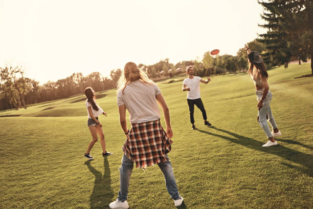 Having fun with friends. Full length of young people in casual wear playing frisbee while spending carefree time outdoors plastic disc stock pictures, royalty-free photos & images