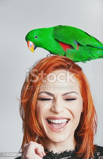 Young woman laughing with her eyes closed while green parrot is standing on her head.