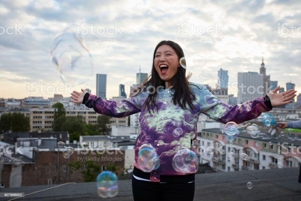 Having fun with soap bubbles. Asian woman standing on the rooftop stock photo
