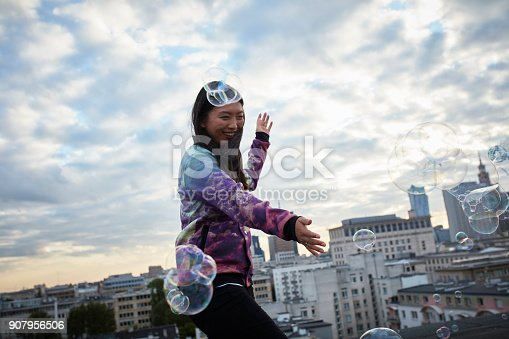 Young woman enjoying view on the roof. catching sopa bubbles