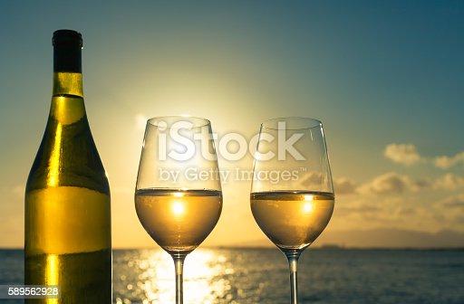 873264516istockphoto Having glass of wine on the beach at sunset 589562928