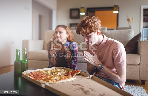 Ginger young couple is having pizza for lunch, they are students so they usually eat fast food. They are a real couple so emotions are real and candid, they are 23 years old. They are eating and watching movies on TV. He is choosing slice of pizza but it is looking like he's having a grace before eating.