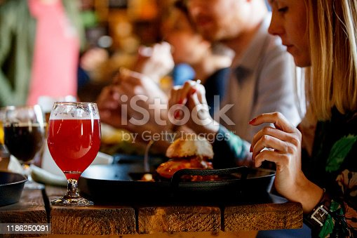 Mid adult woman having lunch and red craft beer with friends in a pub