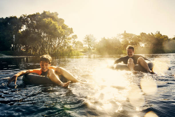 Having such fun today Shot of a father and son enjoying a day outdoors floating on water stock pictures, royalty-free photos & images