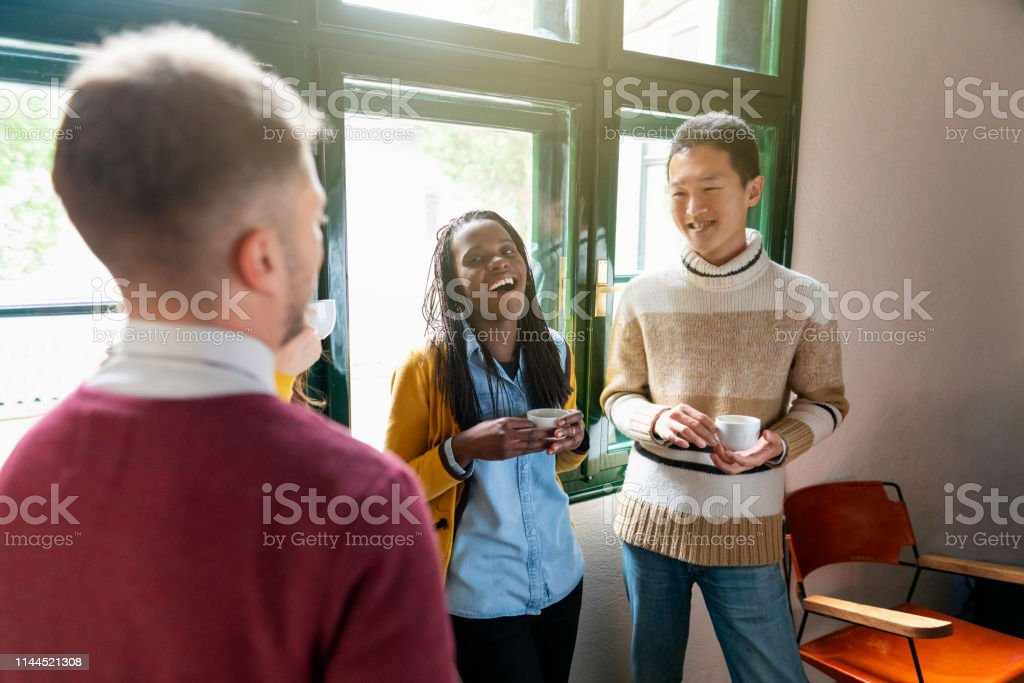 Multi - ethnic group of colleagues drinking coffee and relaxing at...