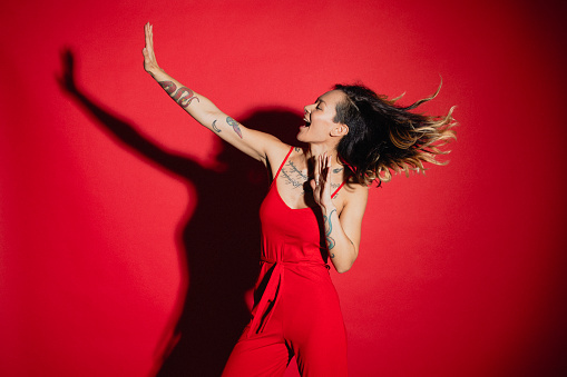 Young woman dressed in a red jump suit dancing in front of a red background.