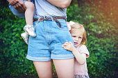 Shot of a little girl holding onto her mother during a day outdoors