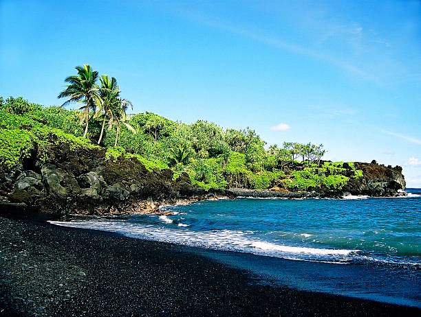 Hawaii Black sand beach and coastline on Maui A black sand beach and green coastline on Maui black sand stock pictures, royalty-free photos & images