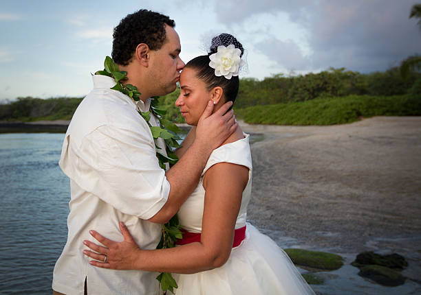 Hawaii Bliss This Polynesian Groom kisses his new Bride on the forehead. neicebird stock pictures, royalty-free photos & images