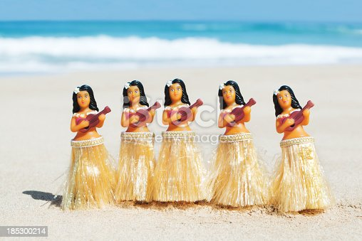 A group of five Hawaiian hula dancer figurines doing the traditional hula dance performance and playing the ukulele on a Hawaiian Island beach on the island of Kauai, Hawaii, USA. Pacific ocean waves are in soft focus in the background. Photographed in a horizontal format with copy space.