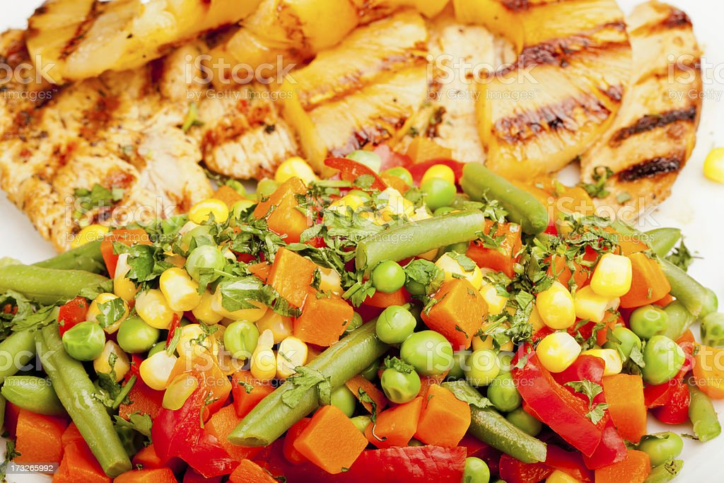 Hawaiian chicken served with mexican salad and pineapple royalty-free stock photo