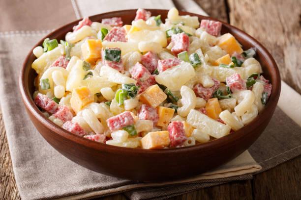 hawaiianische küche: salat mit nudeln, schinken, ananas, zwiebel, cheddar-käse mit mayonnaise nahaufnahme. horizontale, rustikalen stil - hawaiianischer salat stock-fotos und bilder