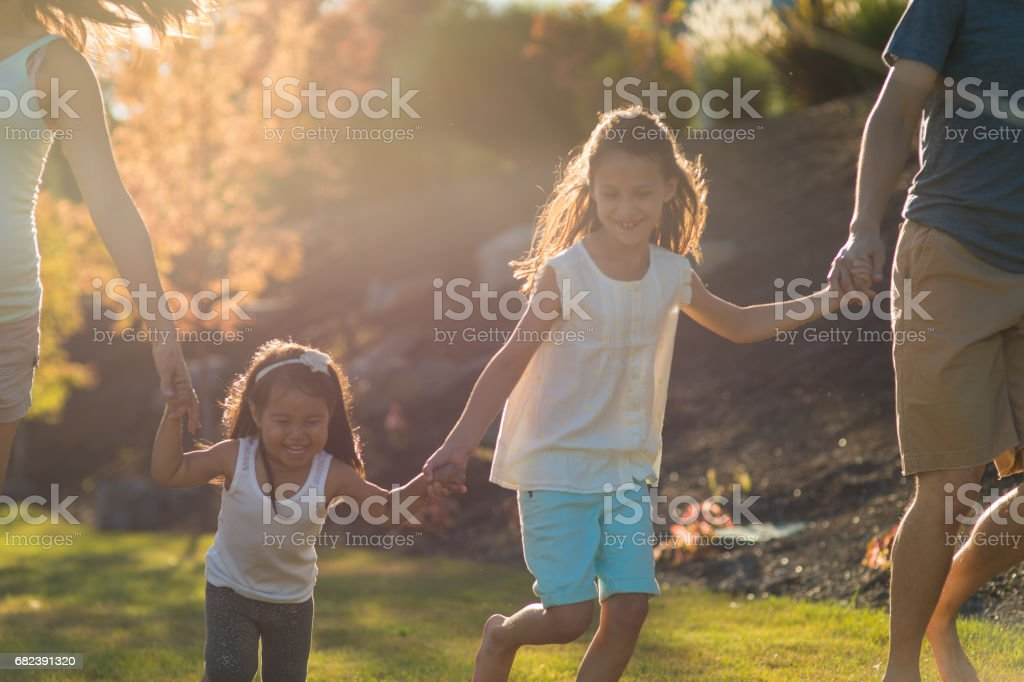Hawaiian family with two young girls runs hand in hand through park on sunny evening royalty-free stock photo