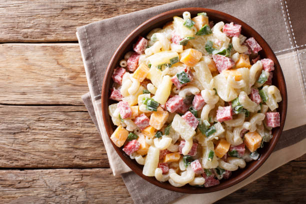 hawaiische nahrung: salat mit nudeln, schinken, ananas, zwiebel, cheddar-käse mit nahaufnahme mayonnaise in eine schüssel geben. horizontale ansicht von oben - hawaiianischer salat stock-fotos und bilder