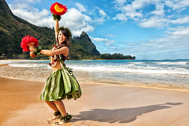 hawaiian hula dancer on beach with red feather shakers - hawaiian ethnicity stock photos and pictures