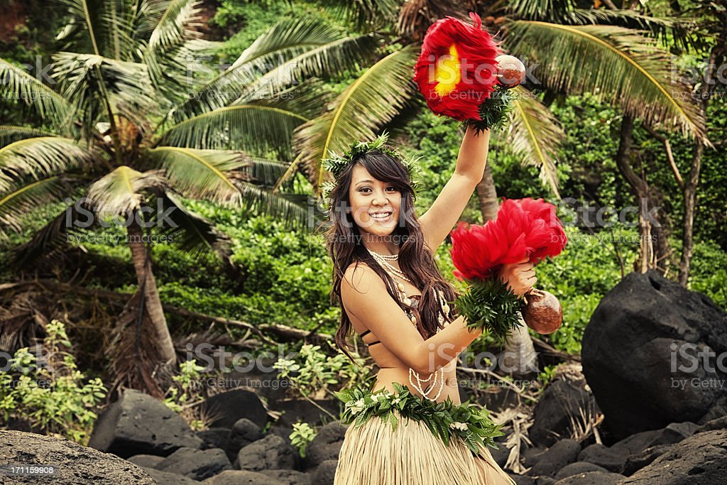 Hawaiian Hula Dancer on Beach with Red Feather Shakers royalty-free stock photo