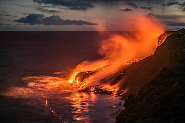 Hawaiian lava flow into the Pacific ocean Spectacular evening view of the lava from the Kilauea volcano, flowing in the Pacific ocean near Kalapana on the south coast of the Big Island of Hawaii. volcano stock pictures, royalty-free photos & images
