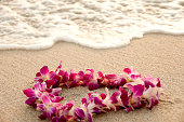 A colorful Hawaiian Lei lying on a sandy beach at sunset with an incoming wave.