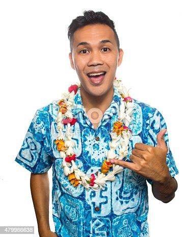 A hawaiian man in a vintage aloha shirt giving a shaka