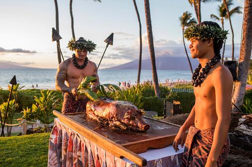 Wailea beach, Maui: Roast pig getting ready by traditionally dressed Hawaiian men during luau on beach in Maui.