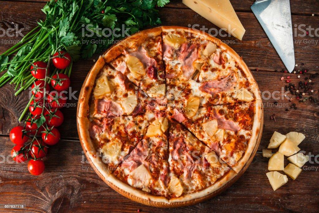 Hawaiian Pizza am rustikalen Holztisch, flach zu legen – Foto