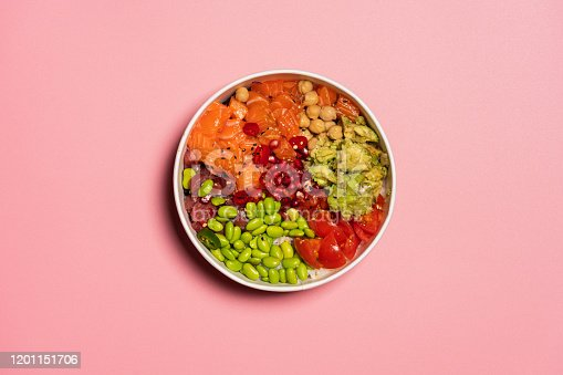 Hawaiian poke bowl with rice, salmon, avocado, tomatoes, tuna, chickpeas, pomegranate and edamame. Top view from above. Pink background for copy space.