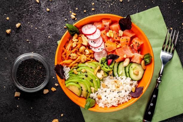 hawaii salat poke mit lachs fisch, avocado, koreanische karotten, gurken, rettich und reis mit schwarzem sesam. in eine orange platte. auf dem schwarzen hintergrund. textfreiraum, ansicht von oben - hawaiianischer salat stock-fotos und bilder