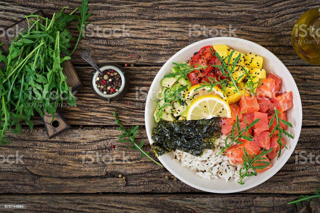 Hawaiian Lachs Fisch Poke Schüssel mit Reis, Avocado, Mango, Tomaten, Sesam und Algen. Buddha-Schüssel. Diätkost. Ansicht von oben. Flach zu legen – Foto
