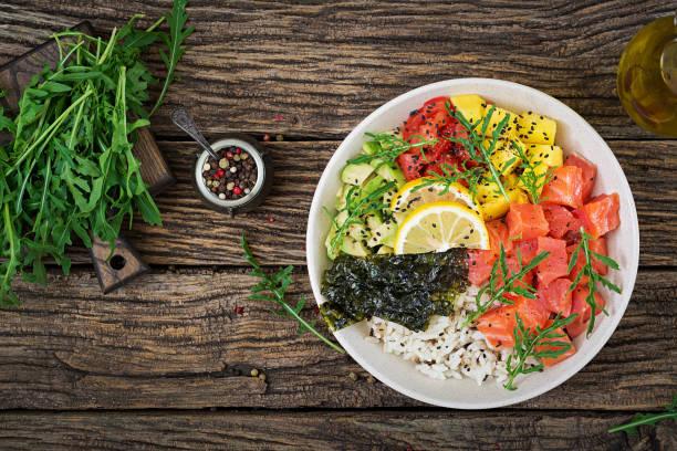 hawaiian lachs fisch poke schüssel mit reis, avocado, mango, tomaten, sesam und algen. buddha-schüssel. diätkost. ansicht von oben. flach zu legen - hawaiianischer salat stock-fotos und bilder