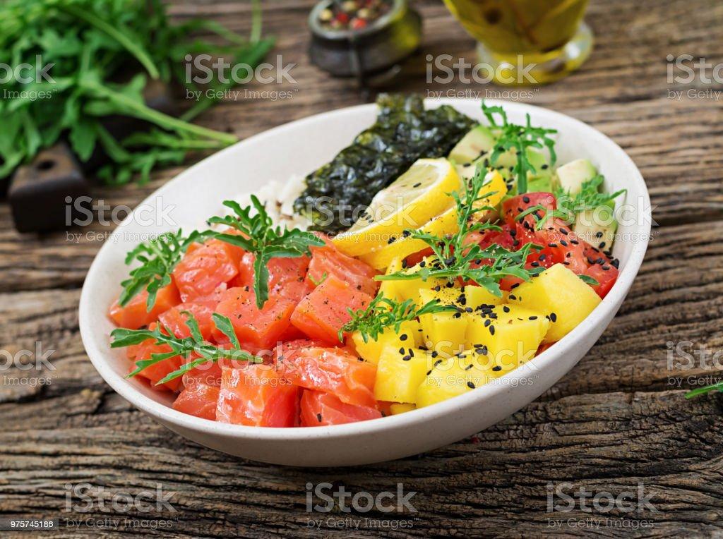 Hawaiian Lachs Fisch Poke Schüssel mit Reis, Avocado, Mango, Tomaten, Sesam und Algen. Buddha-Schüssel. Diätkost. - Lizenzfrei Avocado Stock-Foto